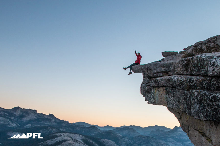 A climber sits on the edge of a cliff, waving. Turn adversity into advantage.
